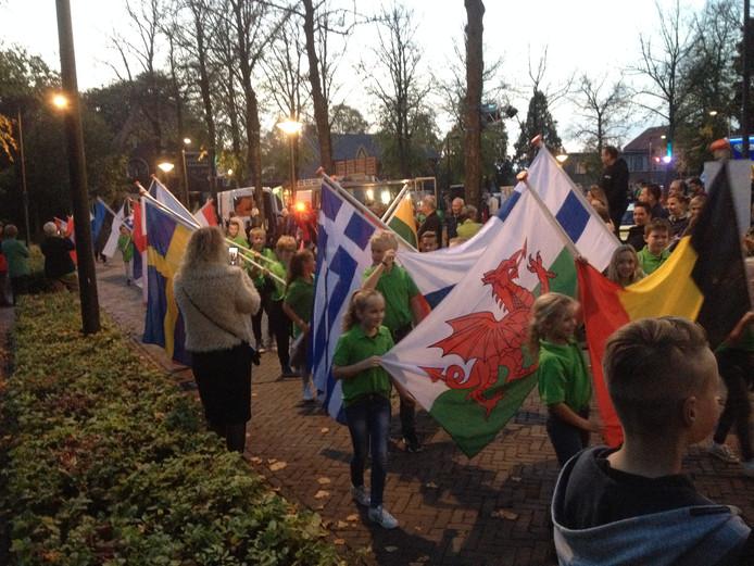 Kinderen dragen de vierenveertig vlaggen rond het plein in Venhorst.