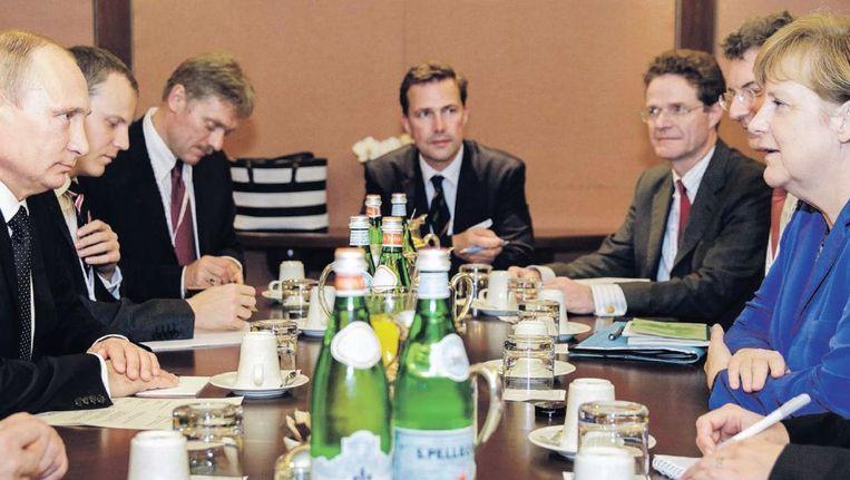 Vladimir Poetin (links) in gesprek met Angela Merkel in een Milanees hotel, tijdens de EU-Azië-top. Beeld reuters