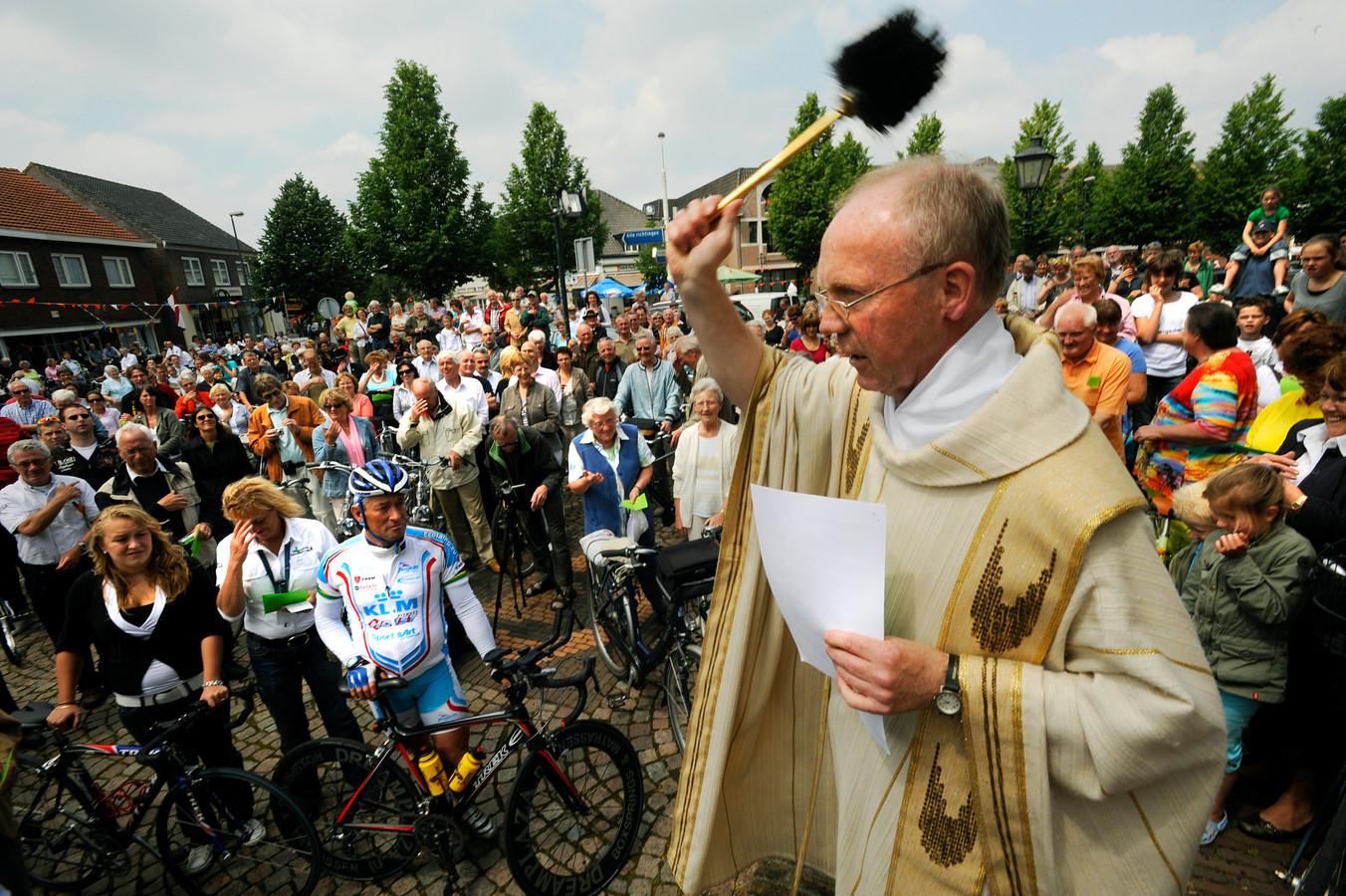 Pastoor Theo te Wierik zegent de fietsen van Guus Moonen en anderen.