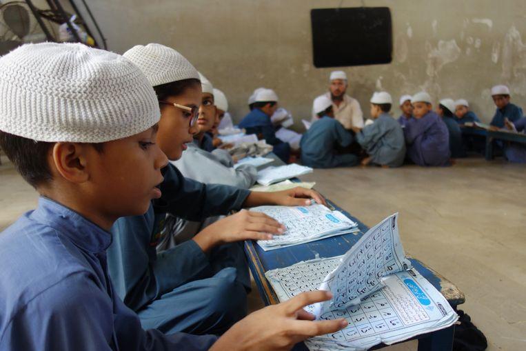 Jongens leren de koran uit hun hoofd in een madrassa, een religieuze school, in de Pakistaanse stad Karachi. Beeld Arjen van der Ziel