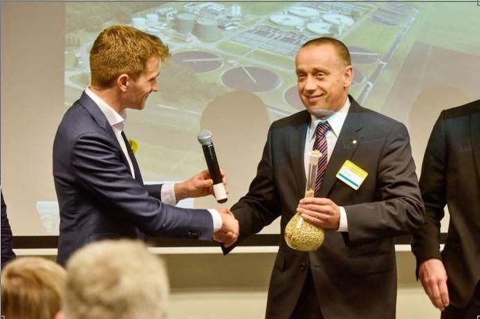 Martin Tietema, directeur van KNN Bioplastics, overhandigt de eerste kilo plastickorrels uit rioolslib aan Joan Hanegraaf (r) van Oerlemans Packaging