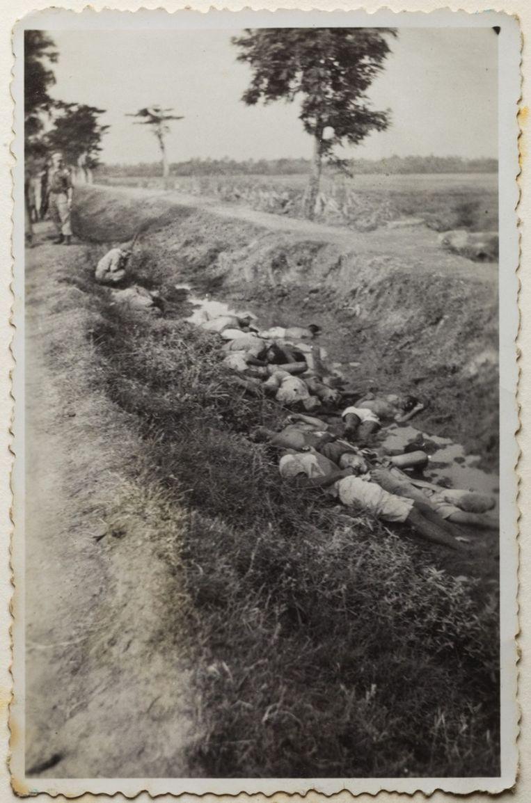 Doden in een greppel, twee Nederlandse soldaten kijken toe. Beeld Album Jacobus R.