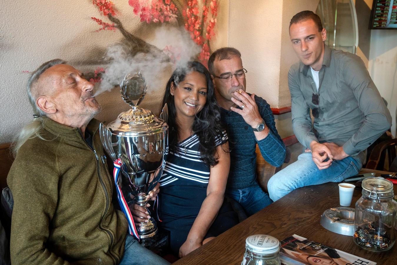 Marjolein de Keijzer-van Nimwegen met de kampioensbeker in coffeeshop Zero Zero temidden van haar vaste klanten (van links naar rechts) Peter Zadina, Uwe von Meeteren en Ricardo van Keeren.