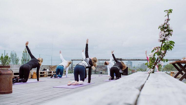 Kijk eens: met Amsterdam op de achtergrond lekker stretchen tijdens Yoga Voor Vroege Vogels op donderdag. Beeld Nest