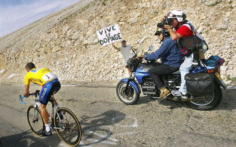 Lance Armstrong in de gele trui tijdens de Tour de France van 2002 op de Mont Ventoux. Een toeschouwer toont op een bord zijn bedenkingen. Beeld AFP