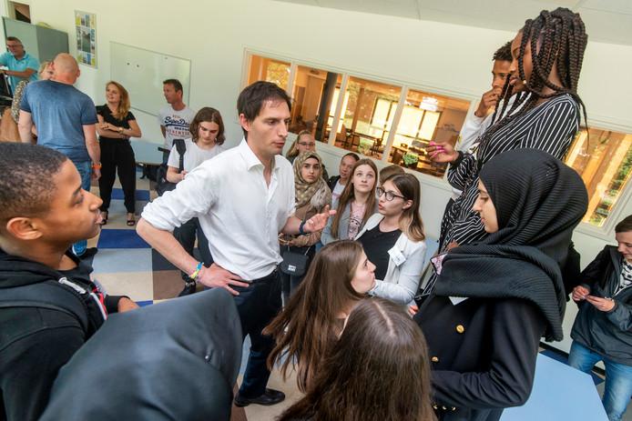 Minister Wopkes geeft de leerlingen instructies voor een goeie groepsfoto. Een deel van de groep heeft inmiddels een afspraak geregeld voor een rondleiding op het ministerie.