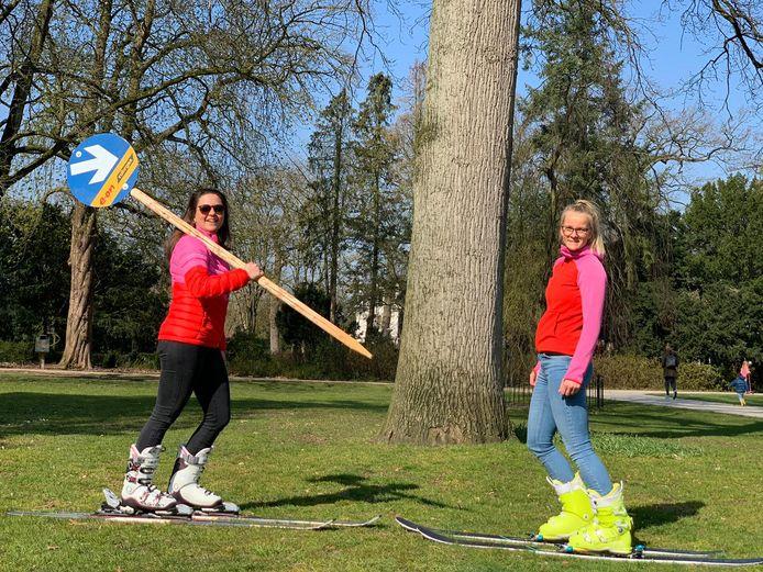 Helga van Dijk (l) en Lusan Meeder banjeren op ski's door de Pekingtuin in Baarn om 1,5 meter afstand te houden.