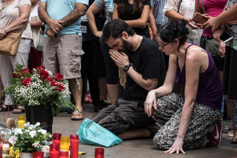 Rouwenden bij een plaats in Barcelona waar kaarsen en bloemen voor de slachtoffers van de aanslag zijn neergezet. Beeld Getty Images