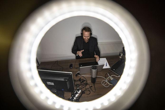Psychiater Bram van der Boom verzorgt in zijn zolderkamer voor collega's uit de zorg een webinar online behandelen.