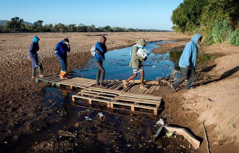 Sjouwers komen na een omweg over de grens, via een oversteek van de rivier Limpopo. Beeld Bram Lammers