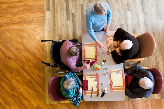 Een vrijwilligster serveert eten in een verzorgingshuis.