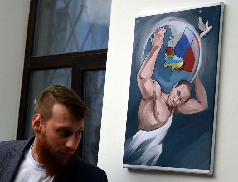 Poetin draagt de wereld op zijn schouders op een schilderij ter ere van zijn verjaardag. Beeld afp