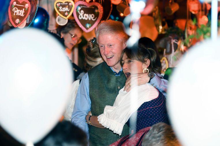 Bill Clinton (l) en een gast in de K'fer marquee, vanavond tijdens het Oktoberfest in München.