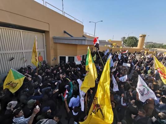 De woedende menigte voor de poort van de Amerikaanse ambassade in Bagdad.