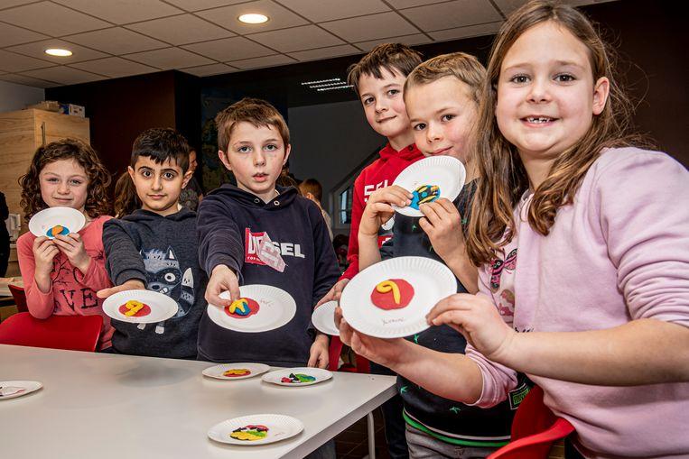 Deze kinderen tonen trots hun knutselwerkjes.