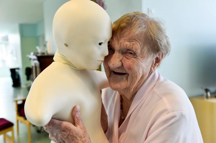 Een hoogbejaarde vrouw omhelst een robot.