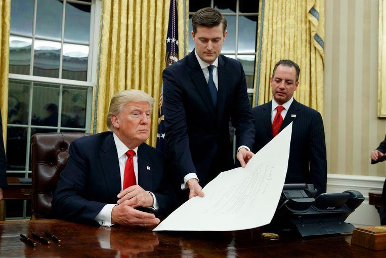 Rob Porter (m.), overhandigt Trump een document in het Witte Huis terwijl toenmalig stafchef Reince Priebus, ondertussen ook ontslagen, toekijkt.