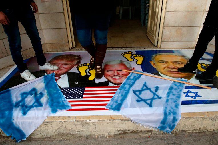 Palestijnen lopen over een foto met president Trump (L), vicepresident Mike Pence en Israëls president Benjamin Netanyahu Beeld AFP