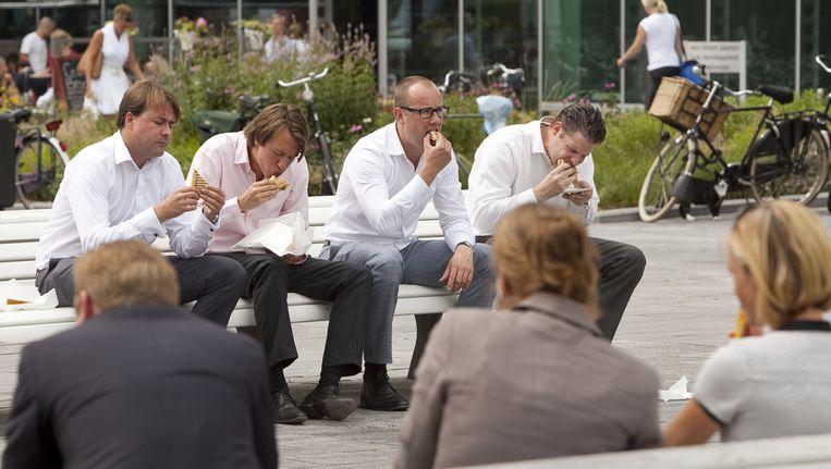 Kantoorpersoneel nuttigt de lunch op het kantorenpark aan de Zuidas in Amsterdam. Beeld null