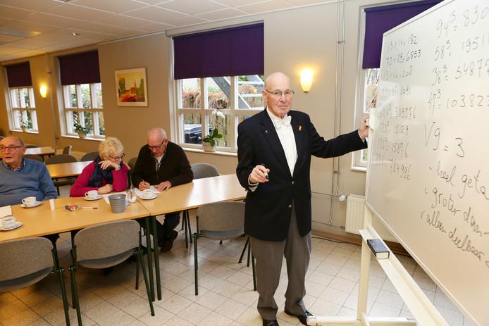 Willem Bouman, met priemgetallenvlinderdas, geeft leeftijdgenoten rekenles.