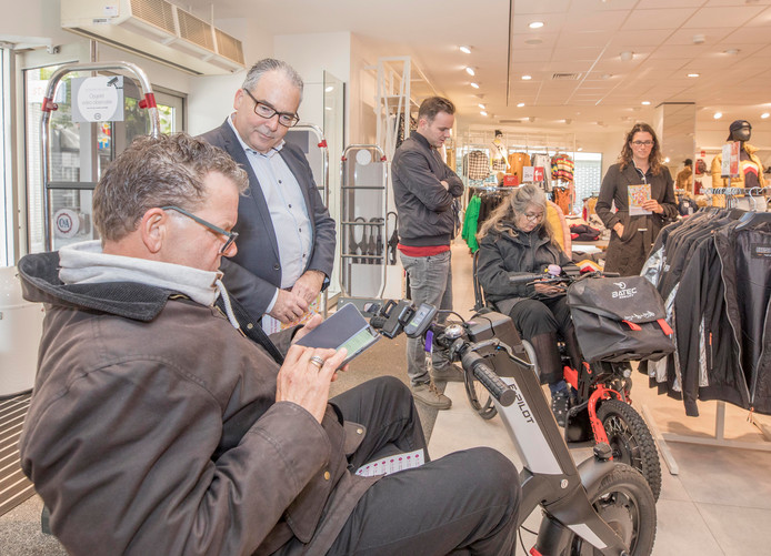 Jan Bas Aertssen (links) verwerkt de toegankelijkheidsscore van C&A op de Ongehinderd-app. Wethouder André van der Reest kijkt toe terwijl Ilze Abramsen (rechts in rolstoel) ook haar score invult.
