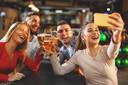 Een groep jonge mensen die plezier hebben met een glaasje bier.