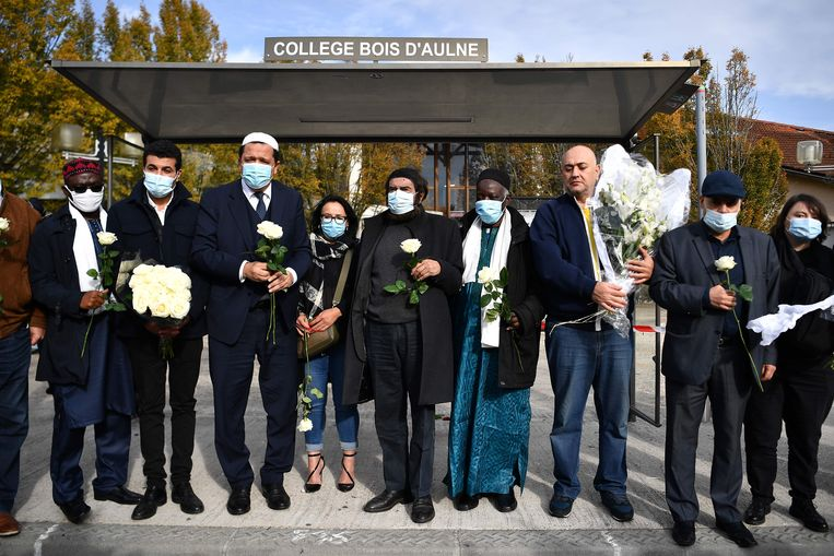 Een groep imams en de joodse schrijver Marek Halter (midden) houden een gezamenlijke protestwake bij de school van de vermoorde Samuel Paty. Beeld AFP
