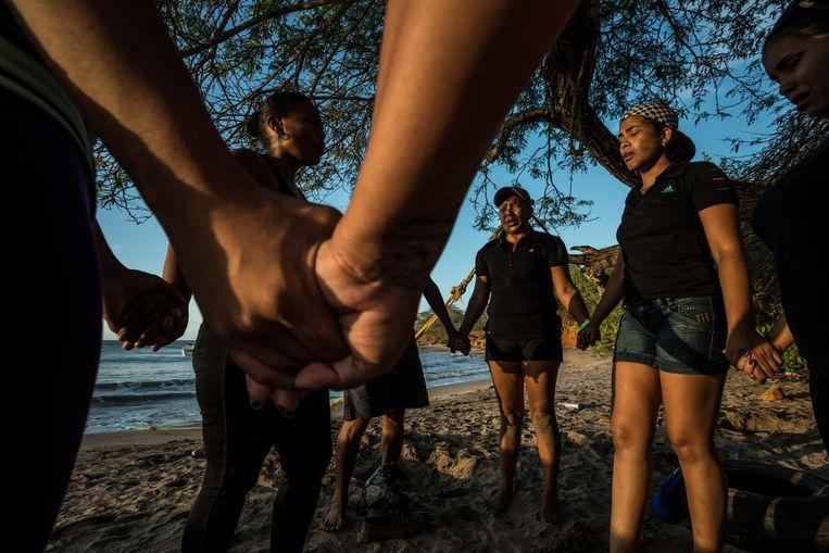 Op het strand van Falcón in Venezuela bidt Maria Piñero (met pet) samen met andere illegale migranten voor een behouden reis naar Curaçao. Beeld Meridith Kohut, The New York Times