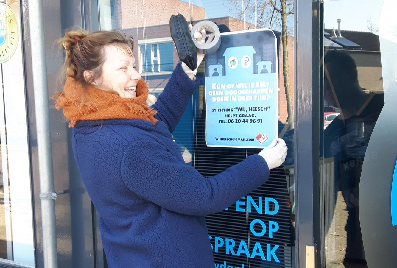 Ingrid ten Broeke hangt een poster op om de hulpactie meer bekendheid te geven.