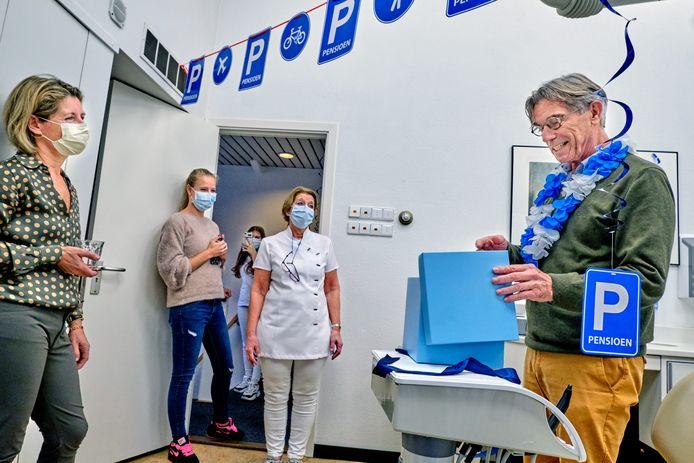 Tandarts Wim (rechts) opent op zijn laatste dag een doos vol met persoonlijke bedankjes van zijn patiënten.