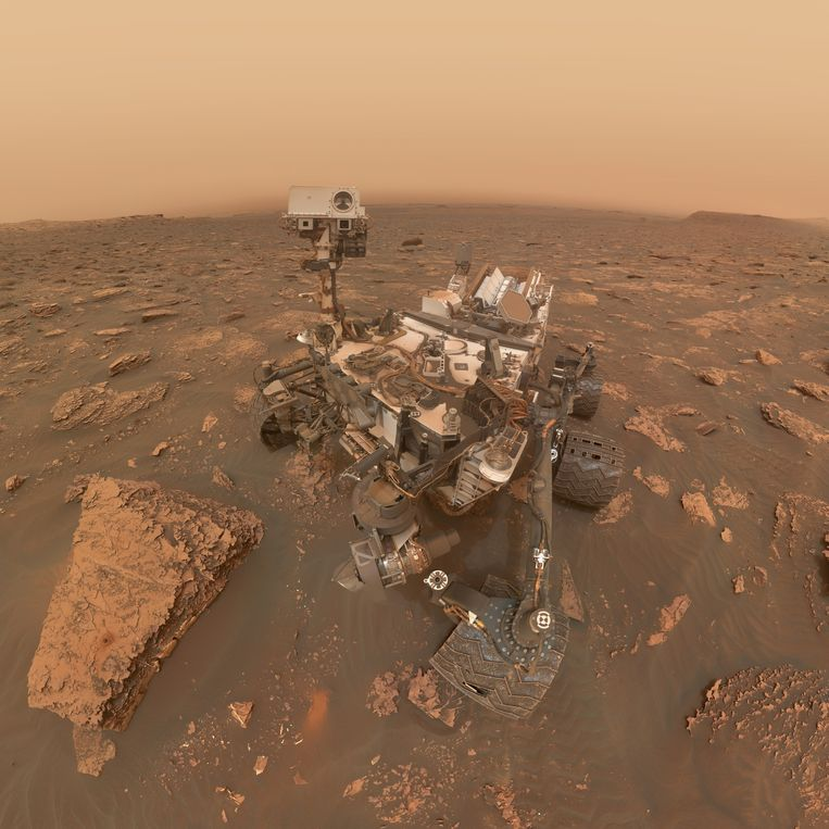 Een selfie van marswagen Curiosity na zes jaar op Mars: de wagen zit onder het zand en de wielen zijn beschadigd Beeld Nasa