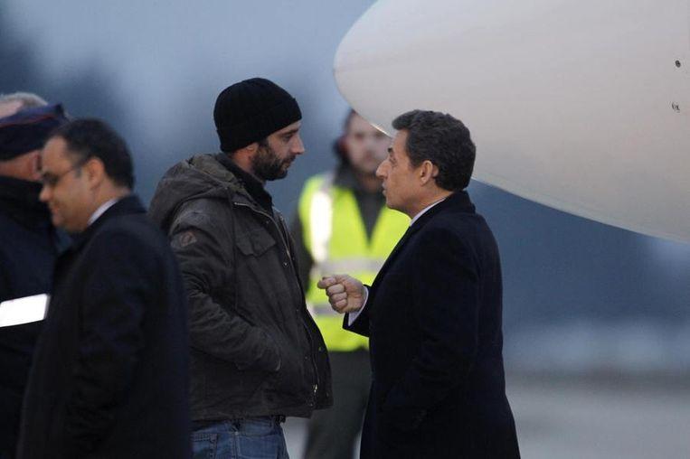 Fotograaf William Daniels (M) spreekt met de Franse president Nicolas Sarkozy (R) na zijn aankomst in Frankrijk. Beeld reuters