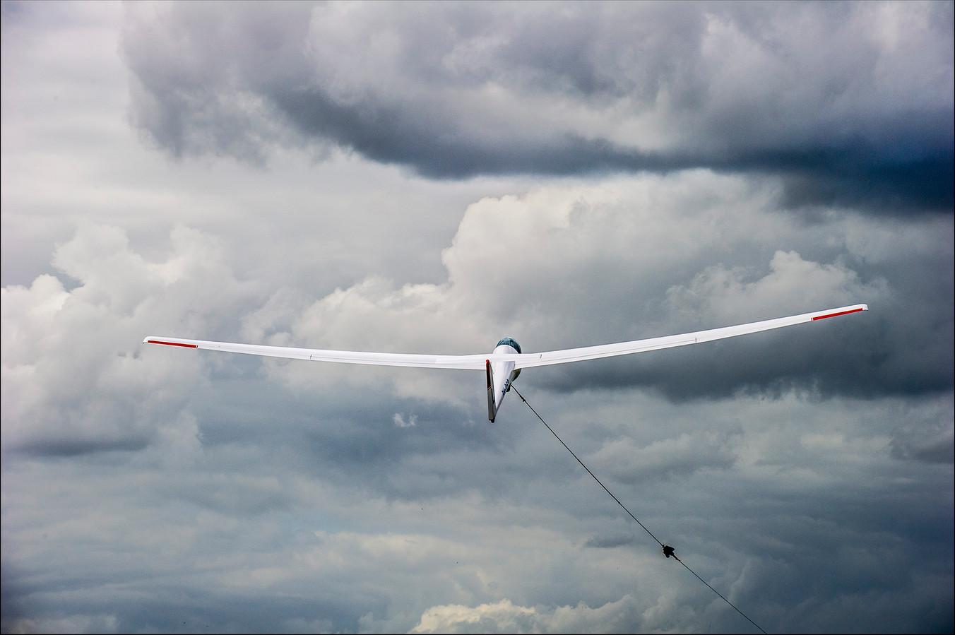 Een zweefvliegtuig wordt via een lier de lucht ingetrokken.