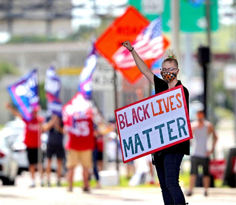 Een Black Lives Matter-demonstrant bij een rally van de Amerikaanse president Donald Trump in Florida. Beeld AP
