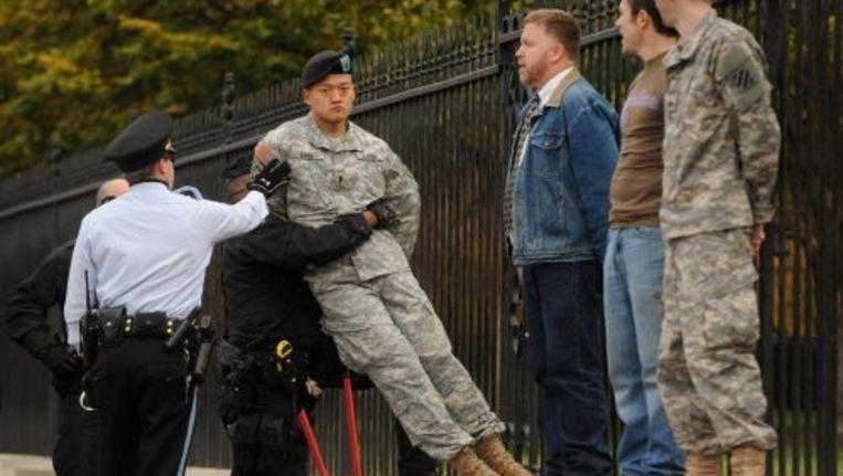 Dan Choi, een homoseksuele Amerikaanse militair, wordt bij het Witte Huis verwijderd na een protestactie. EPA Beeld