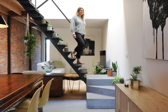 De stalen trap met betonnen voet is een blikvanger die de open woonkamer in tweeën deelt. Voor een knus effect is het plafond in de zithoek verlaagd en ligt er een houten vloer.