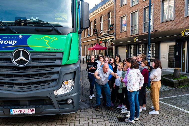 De leerlingen van het Sint-Jozefsinstituut leren de gevaren van de dode hoek naast een echte vrachtwagen.