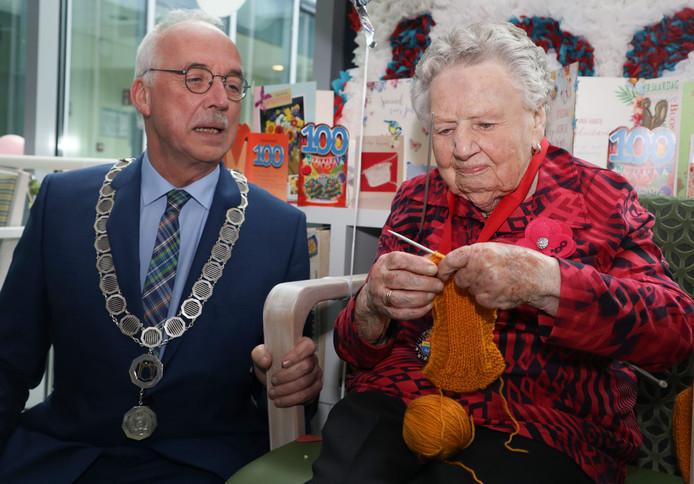 De 100-jarige Maria Taelman-de Smet demonstreert haar breikunsten aan burgemeester Jan-Frans Mulder.