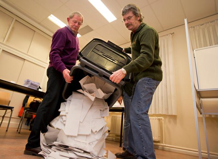 Leden van een stembureau maken zich op voor het tellen van stemmen.