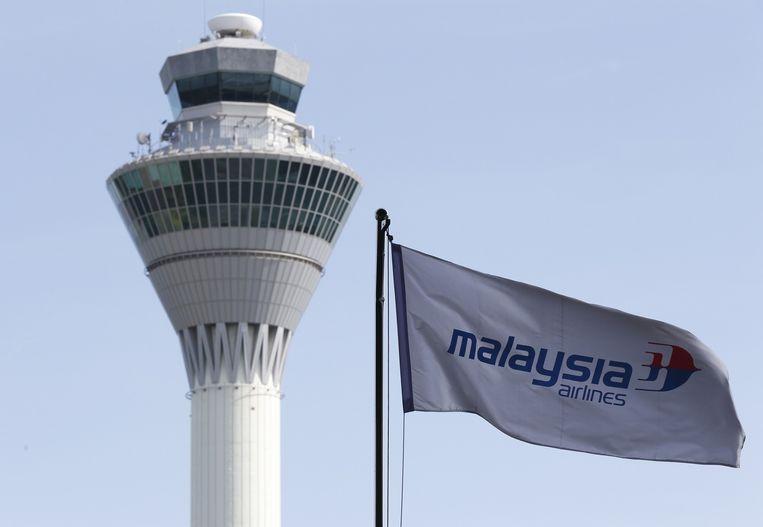 Een vlag van Malaysia Airlines wappert voor de luchtverkeerstoren van het vliegveld van Kuala Lumpur.
