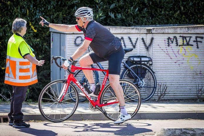 Een verkeersregelaar vertelt een fietser dat hij niet verder mag. Het Zuid-Limburgse heuvelland is afgesloten voor dagtoeristen.