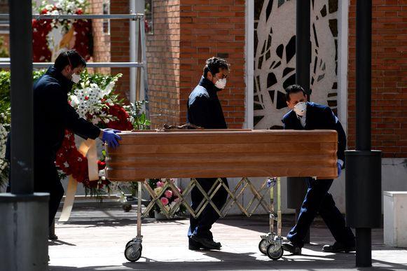 Een kist met daarin het lichaam van een corona-dode wordt een crematorium nabij Madrid binnengereden.