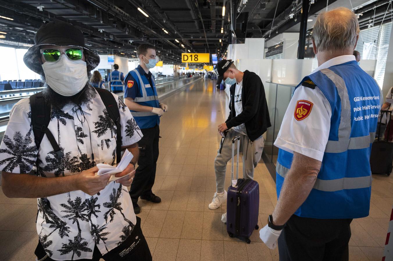 Medewerkers van de GGD ondervragen reizigers op luchthaven Schiphol. Reizigers uit risicogebieden worden achter de douane gecontroleerd op coronaklachten.