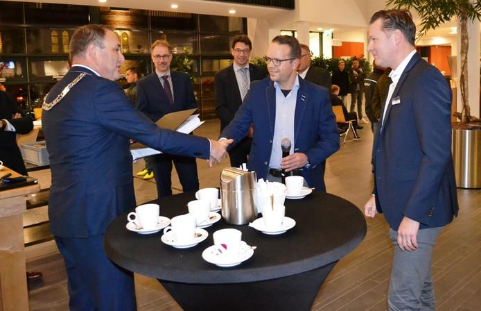 Wethouder Ben Beens neemt de 5578 handtekeningen in ontvangst van de supermarktondernemers Ten Have (Albert Heijn Holten) en Haanstra (Coop Holten).