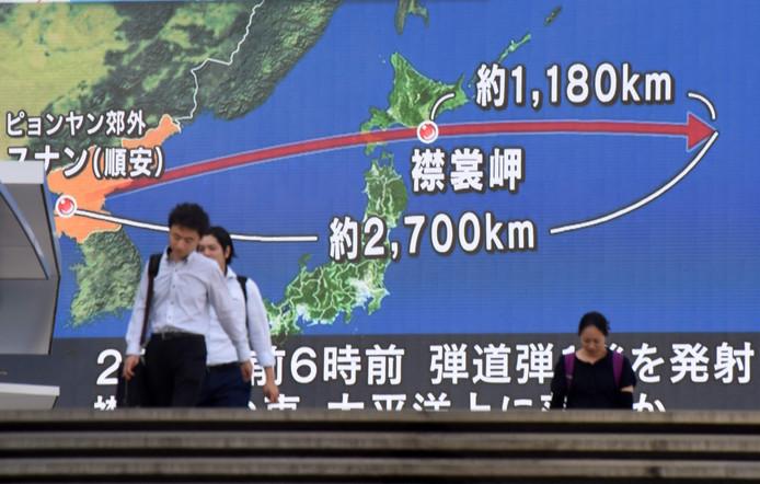 Inwoners van Tokio wandelen langs een groot tv-scherm waarop de laatste Noord-Koreaanse test in kaart wordt gebracht.