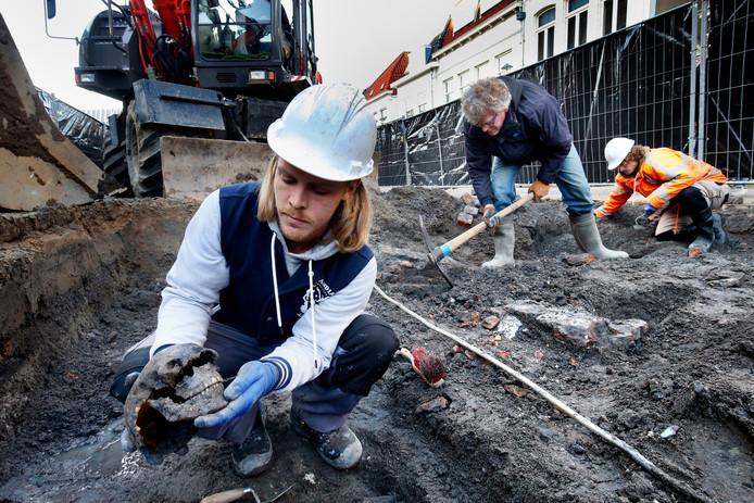 Joris Brattinga heeft zojuist in delen een schedel opgegraven. Achter hem collega-archeoloog Pieter Floore en daarachter Niels Tuinman van Hollandia Archeologen.