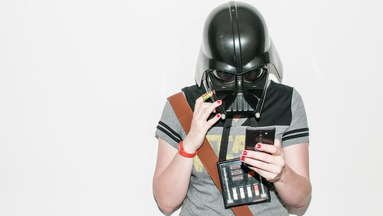 Darth Vader kijkt op zijn smartphone. Beeld null
