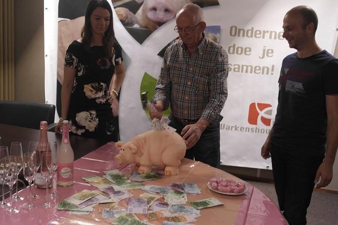 Willie van Gemert (midden) slaat het spaarvarken stuk en start daarmee symbolisch de uitbetaling van de Aujeszky-rente. Links NVV-voorzitter Ingrid Jansen en rechts NVV-secretaris Frank Donkers.