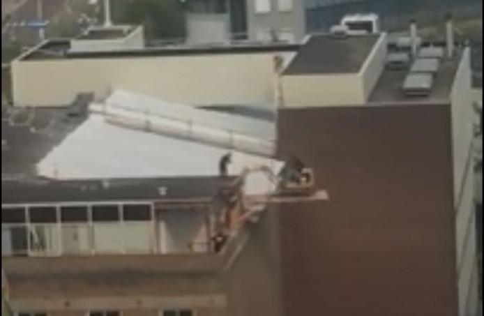 Graafmachine bungelt boven C&A gebouw in Eindhoven.