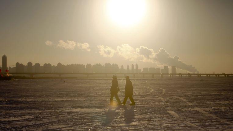 Mensen lopen over de bevroren Songhua-rivier in China. Beeld afp